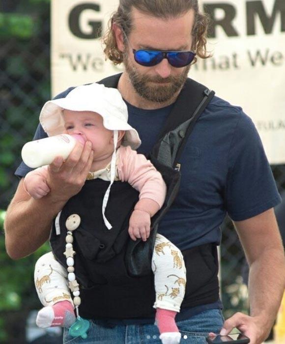 娘レアちゃんにミルクをあげながら、携帯を弄ってるブラッドリー・クーパー